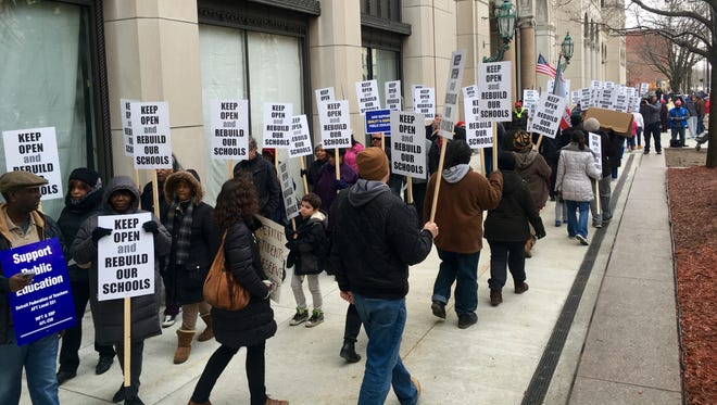 Hundreds of educators, parents and other community members marched outside the Cadillac Place building Friday afternoon to protest the state's plan to close 38 Michigan public schools as early as this summer.