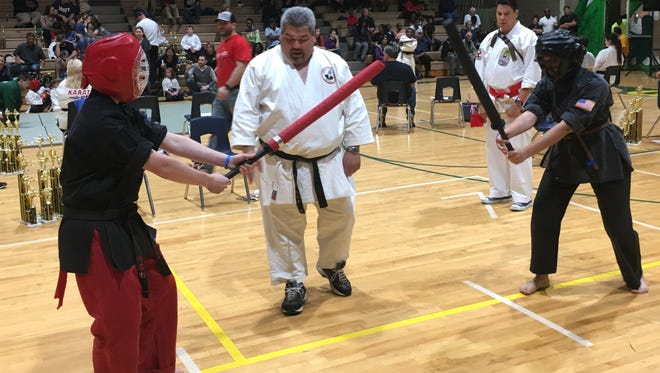 Black belt Damian Jeansonne (left), referee Ron Carter and black belt Dazani Jackson compete in a recent meet.