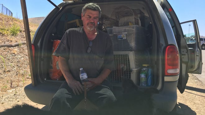 Scott Klempner of Dewey eats outside the animal shelter at Bradshaw Mountain High School on June 28, 2017. The shelter was at capacity, so he planned to spend the night in his camper with his two dogs. He still had to take seven parrots to another shelter several miles away.
