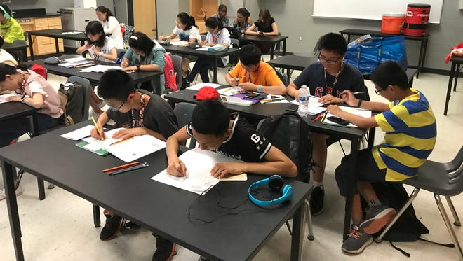 Students work on activities during the Chinese Exchange Camp, a summer program hosted by Wicomico County Public Schools, at James M. Bennett High School on July 14, 2017.