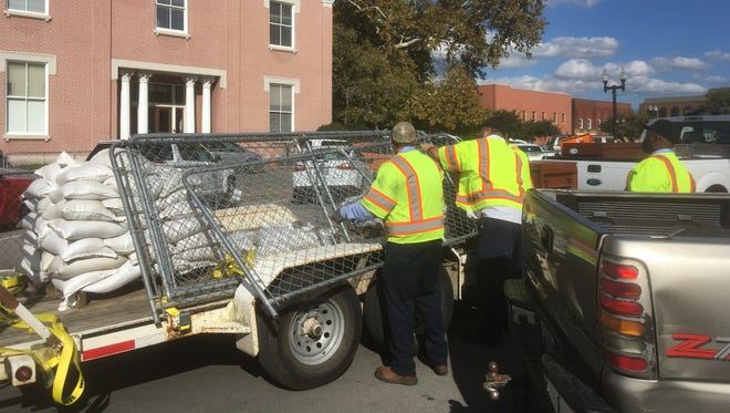 Crews grab portable fencing Friday afternoon to build a barricade around the center of the Rutherford County Courthouse Square to keep opposing protesters separated. Oct. 27, 2017.