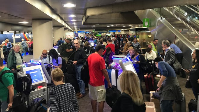 Passengers wait at Phoenix Sky Harbor International Airport on Nov. 8, 2017, after a suspicious package closed two security checkpoints and two ticket counters in Terminal 4.