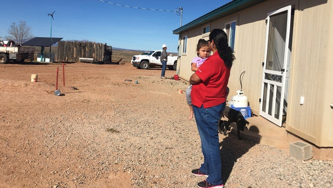 This undated photo provided by the Navajo Tribal Utility Authority, shows Annie Hamm holding her great granddaughter outside her home on the Navajo Nation near Montezuma Creek, Utah. Hamm and her husband recently got electricity to their home, in time for the holidays.