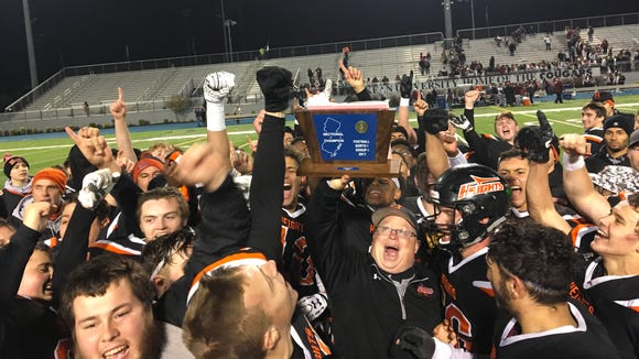 Players surround Hasbrouck Heights football coach Nick Delcalzo after winning the program's second straight North 1, Group 1 title.