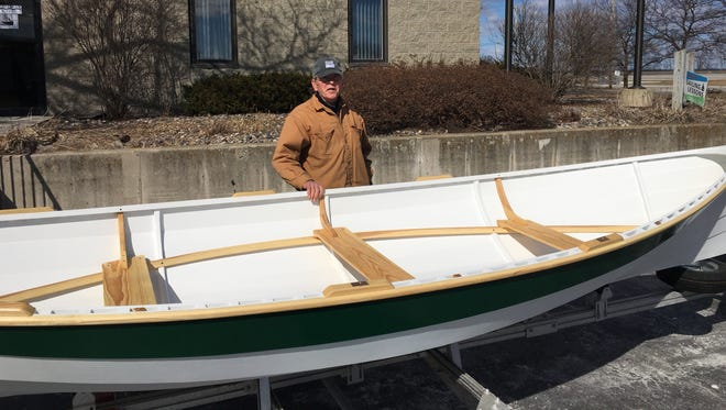 Rodger Swanson stands with a replica Mackinaw  rowboat built by Hands on Deck, a non-profit organization matches mentors and youths for boat-building projects. Swantson, a Hands on Deck volunteer, found historical plans from the 1880s on which the replica was based.