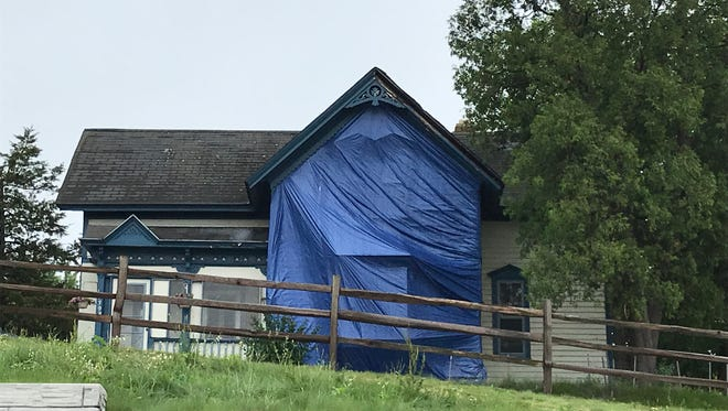 A tarp covers the damaged portion of a house that emergency responders believe started on fire after lightning struck June 18 in New Berlin. Fire officials said the damage is not significant.