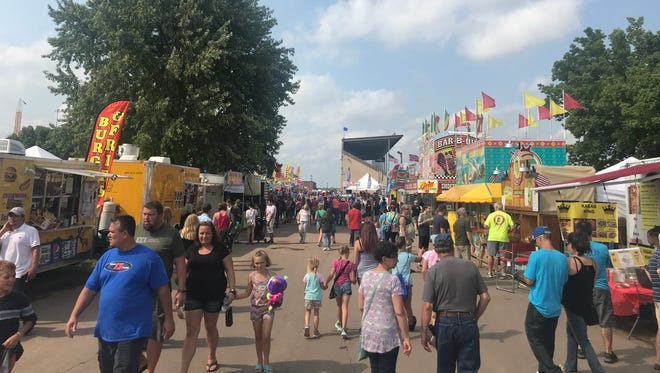 Crowds of people walk alongside dozens of people at the Sioux Empire Fair
