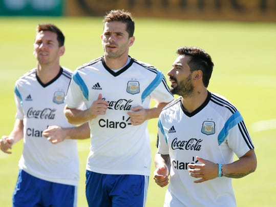 Argentina's Ezequiel Lavezzi, right, jogs with teammates Lionel Messi, left, and Fernando Gago, center, during a training session in Vespesiano, near Belo Horizonte, Brazil, Saturday, June 28, 2014.  Argentina plays in group F of the 2014 soccer World Cup. (AP Photo/Victor R. Caivano)