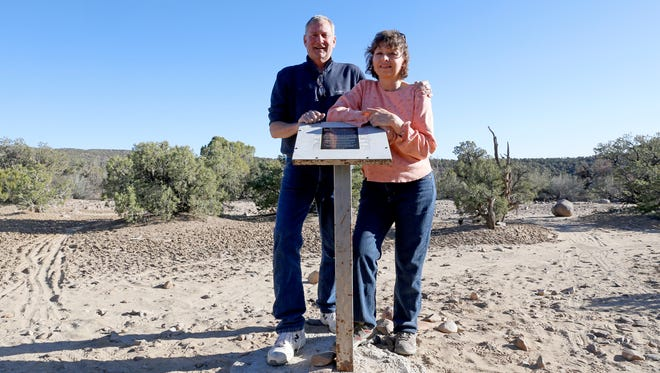 "Scott and Susan Ramsey, stand for a photo in March at a plaque they placed to mark the ""UFO Aztec Incident"" at Hart Canyon near Aztec."
