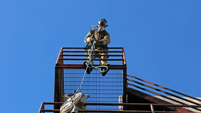 Brandon Armstrong pulls a hose to the top of the San Juan College fire tower on Jan. 23, 2015. The college plans to demolish the fire tower and build a larger one at a different location.