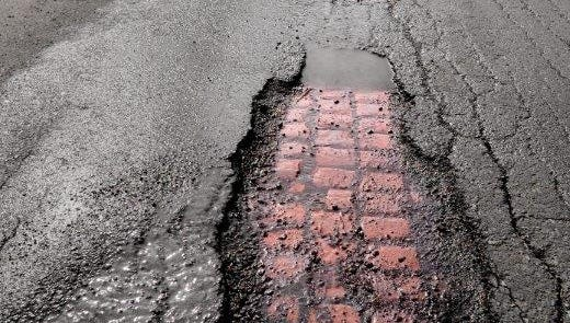 Asphalt pavement used to cover old brick rapidly deteriorates after a winter of severe weather conditions across the region.