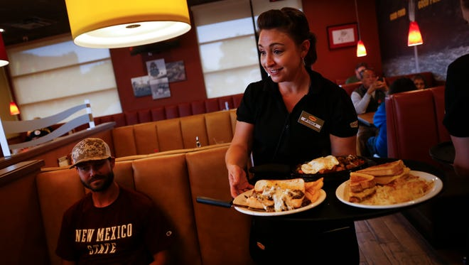 At right, Denny's server Robin Pedigo serves lunch to Joe Kelly, left. Wednesday, Sept. 27, 2017 at Denny's in Farmington.
