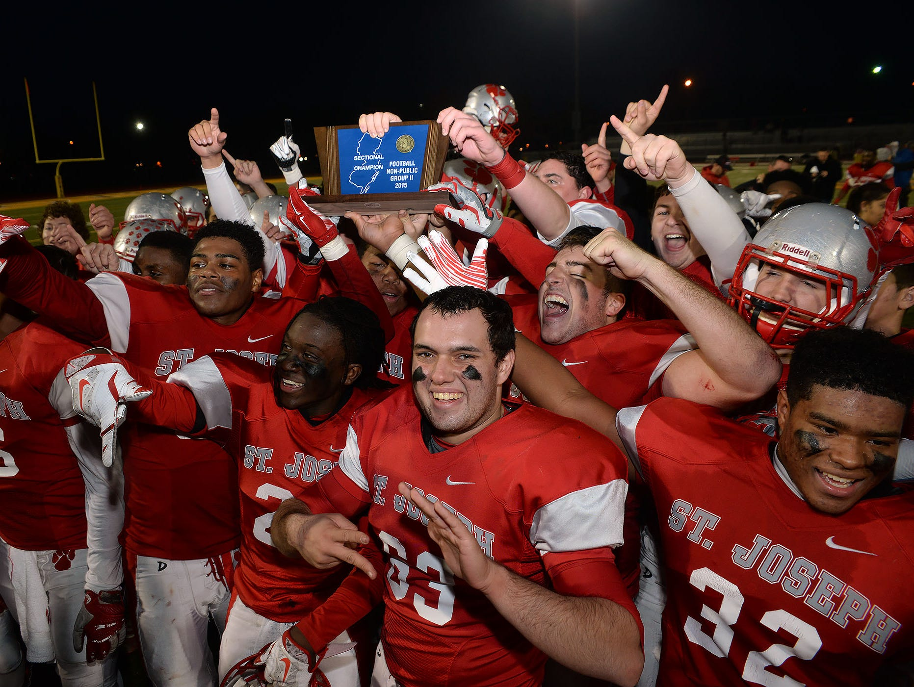 The St. Joe football Wildcats celebrate with the NJSIAA Non-Public Group 2 Championship trophy after their defeat of Hudson Catholic, Sunday, Dec. 6 at Rowan University in Glassboro.