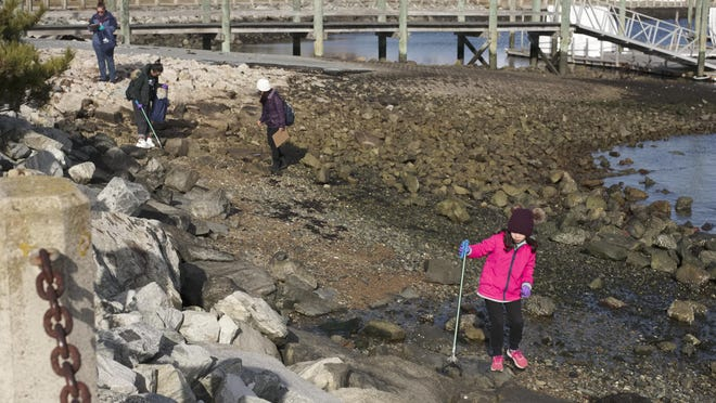 Children and adults walk the shoreline looking for litter during a Clean Ocean Access beach clean up at Fort Adams State Park.