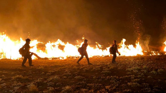 Firefighters walk past flames burning in the brush in California Valley Tuesday night.