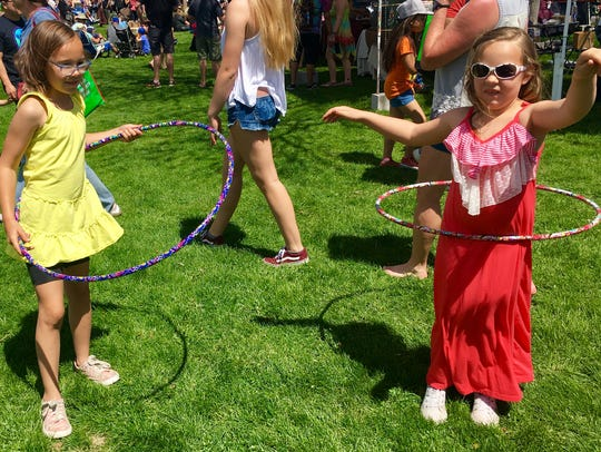 Sisters Brodie, 8, and Nola Ogden,6, try out hula hoops at the Reno celebration of Earth Day on April 22, 20