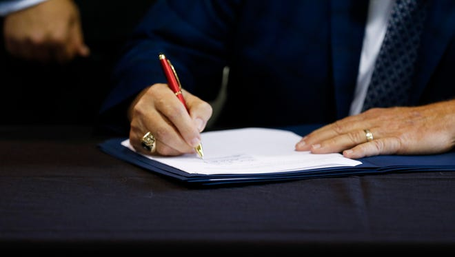 Missouri Gov. Mike Parson signs a bill into law at Hartman & Company on July 12, 2018. Parson signed a slew of bills into law Tuesday, with more to come later in the week.