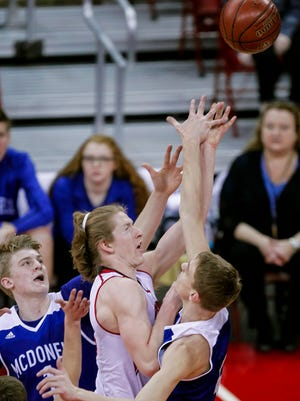 Shullsburg's Hunter Matye shoots between Chippewa Falls McDonell's Grayson Knowlton (left) and Alex Ohde during a Division 5 semifinal in the WIAA boys' state basketball championships.