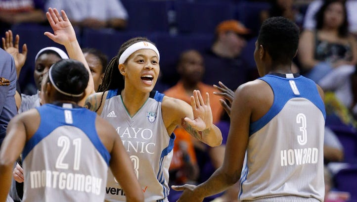 Minnesota Lynx's Seimone Augustus, middle, celebrates with Renee Montgomery (21) and Natasha Howard (3) as the Lynx take an early lead against the Phoenix Mercury during the first half of a WNBA basketball game Wednesday, May 25, 2016, in Phoenix.