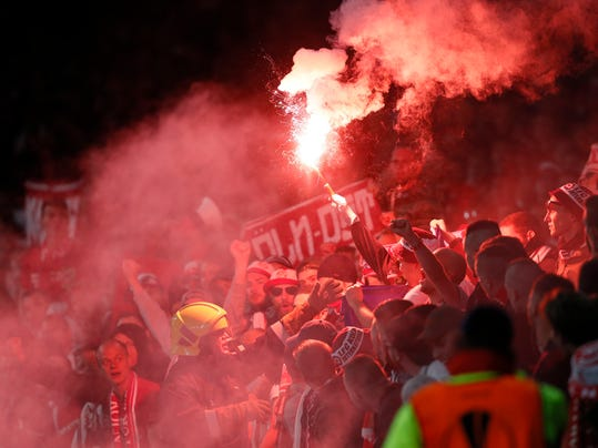 Cologne supporters light fireworks during the Europa League group H soccer match between Arsenal and FC Cologne at the Emirates stadium in London, England, Thursday, Sept. 14, 2017 . (AP Photo/Kirsty Wigglesworth)