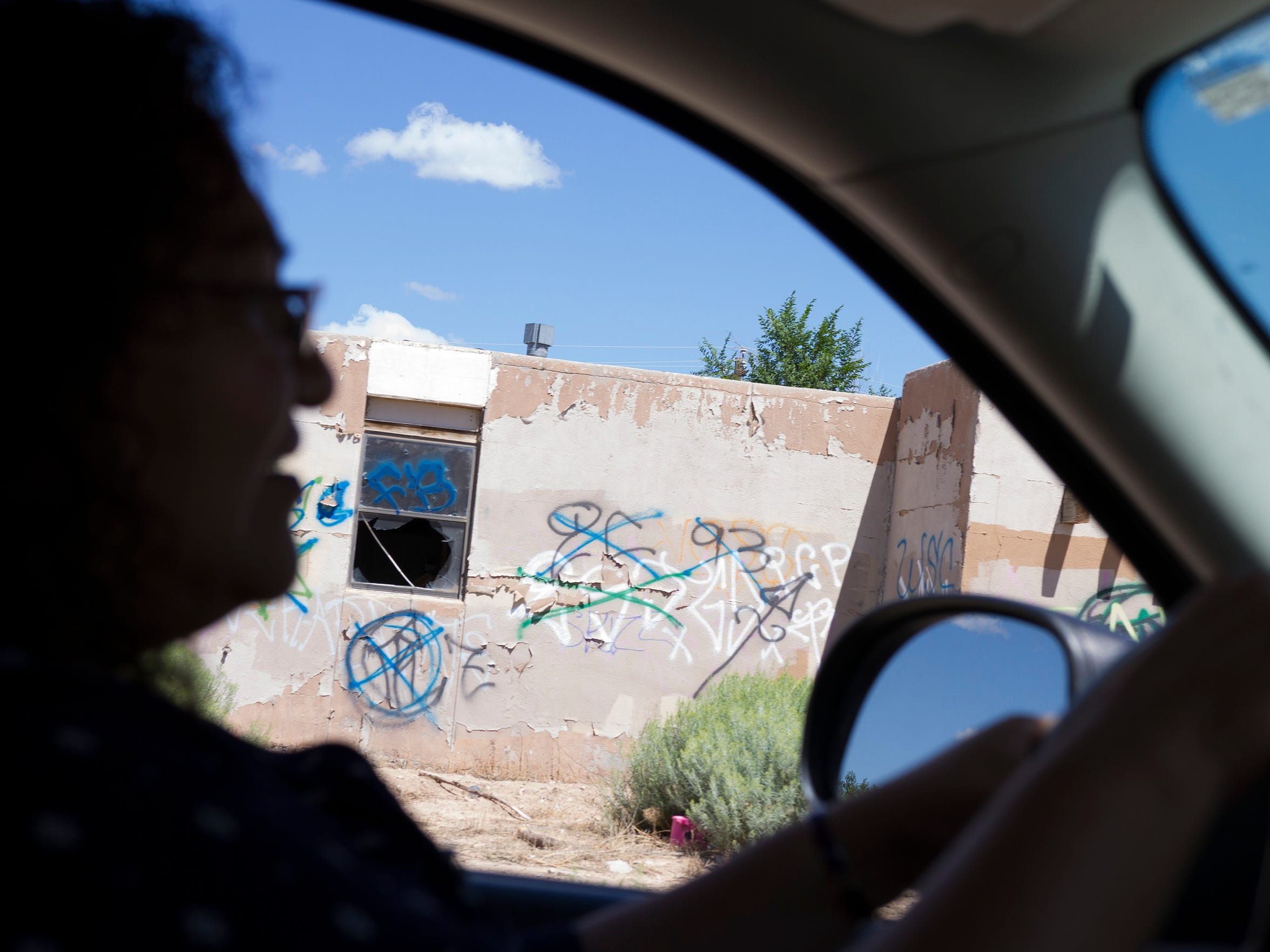 Dina Haven drives past abandoned buildings across the