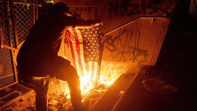 A  Black Lives Matter protester burns an American flag outside the Mark O. Hatfield United States Courthouse on Monday, July 20, 2020, in Portland, Ore. Several hundred demonstrators gathered at the courthouse where federal officers deployed teargas and other crowd control munitions.