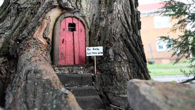 "The ""whimsy house,"" as it's called by creators Dannette and Brad Holifield, had its own miniature for sale sign when the couple put it on the market in early August. The ""house,"" which is partially carved into a tree base, has attracted attention around the Jackson Oaks for its ever-changing decorations based on the seasons."