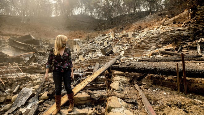 Pam, who declined to give a last name, examines the remains of her partner's Vacaville, Calif., home on Friday, Aug. 21, 2020. The residence burned as the LNU Lightning Complex fires ripped through the area Tuesday night.