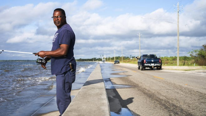 Paul White, of Waveland, takes advantage of the high tide and a slight wave surge from Hurricane Sally's winds to fish from the sea wall as Gulf waters begin to flood onto Beach Boulevard in Bay St. Louis, Miss., Monday, Sept. 14, 2020.