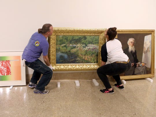 David Hill (left) and Barbra Tharas move a piece of art as they prepare for the Guild Hall: An Adventure on the Arts exhibit Friday, Jan. 20, 2017, at the Art Museum of South Texas in Corpus Christi.