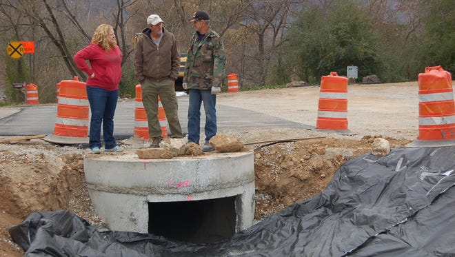 Norfork business owners Kendra Woods (left) and Paul Price (center) discuss safety concerns surrounding a new drainage ditch with Norfork Fire Chief Frankie Baker on Friday. All three say they'd like to see the state install a pipe and cover it.