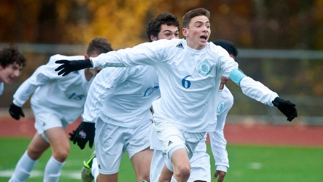 South Burlington's Alex Pasanen celebrates after scoring the equalizer with 8.4 seconds left in regulation against Essex to send the match into overtime during the Boys' Division 1 state championship in Burlington on Saturday, November 1, 2014.