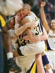 Pacer Rik Smits, left, is mobbed by teammate Reggie Miller and Mark Jackson after Smits hit a 15-footer at the buzzer to defeat Orlando 94-93. The win tied the series at 2-2 in the Eastern Conference Finals at Market Square Arena. Pacer Byron Scott is at right.