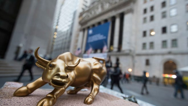 """FILE - In this Tuesday, Oct. 25, 2016, photo, a miniature reproduction of Arturo Di Modica's """"Charging Bull"""" sculpture sits on display at a street vendor's table outside the New York Stock Exchange, in lower Manhattan. Most U.S. investment funds rose in the third quarter."""