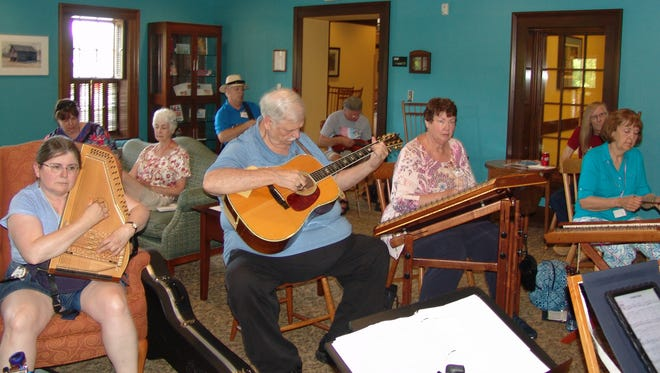 Musicians play together during a jam in the parlor at COTC during the 44th annual Coshocton Dulcimer Days Festival.