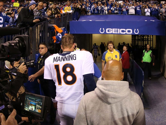 Denver Broncos quarterback Peyton Manning (18) walks off the field after the game against the Indianapolis Colts at Lucas Oil Stadium.