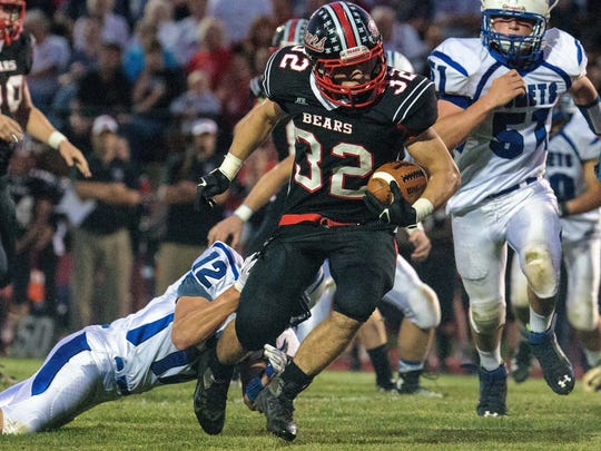 """West Branch's Luke Lenoch (32) runs the ball past Bellevue's Chad Olson (12) during the first half of play in West Branch at the """"Little Rose Bowl"""" on Friday, September 26, 2014. (Justin Torner/Freelance for the Press-Citizen)"""