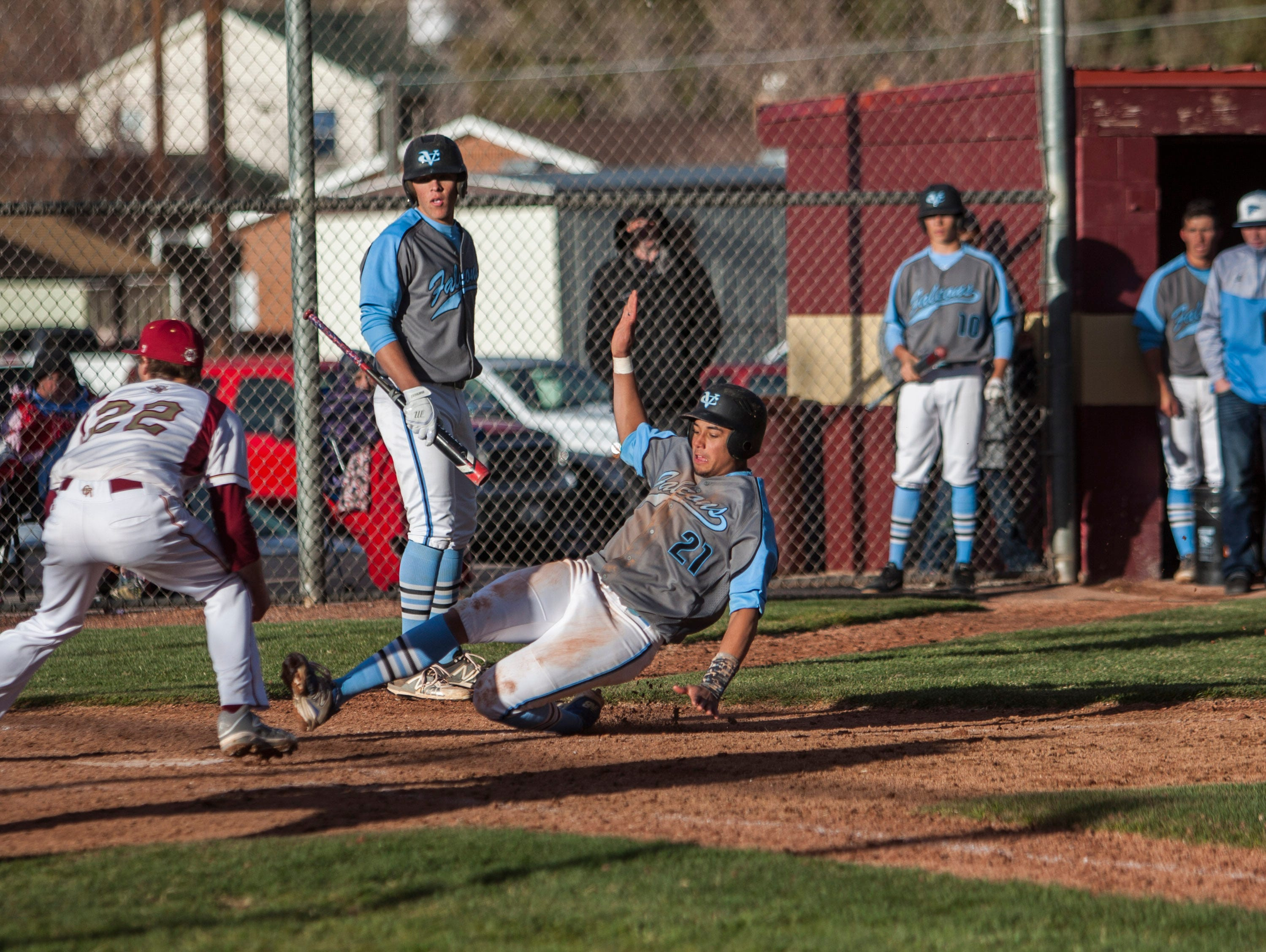 Canyon View's Xavier Stoker slides into home plate to score a run for the Falcons during the game at Cedar High, Thursday, Mar. 31, 2016.