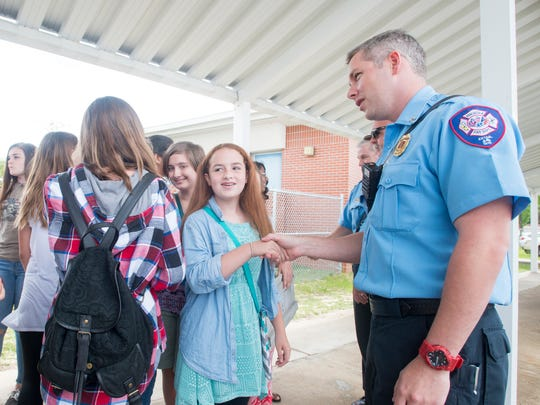 Seventh-grade violinist Grace Knapp, 12, thanks Capt. Dustin Merritt and his fellow Pensacola firefighters at Workman Middle School in Pensacola on Wednesday, May 23, 2017.  The firefighters put out the blaze that destroyed the school's orchestra room on May 13, 2017.