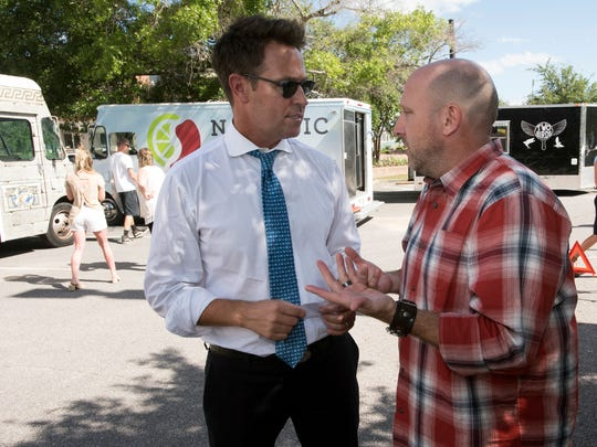 """Mayor Ashton Hayward, left, chats with Peter Woronov, co-executive producer of """"The Great Food Truck Race,"""" before the filming of the Food Network TV show on Wednesday, May 24, 2017, in downtown Pensacola."""