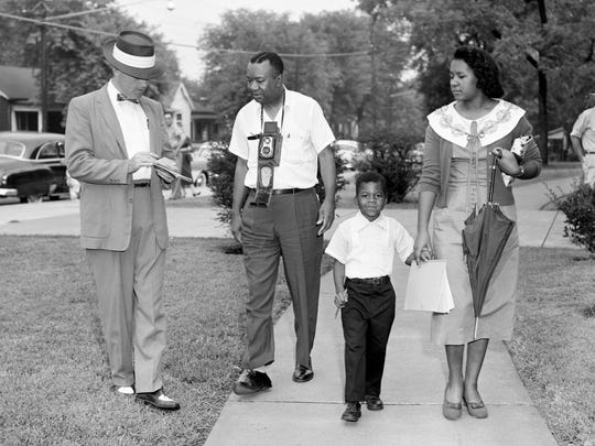 First-grader Marvin Moore, now Marvin Williams, holds the hand of his mother Maud Baxter, as his father talks with a reporter Sept. 9, 1957. They are heading to the all-white Jones School to be one of four students to integrate it on the first day of school.