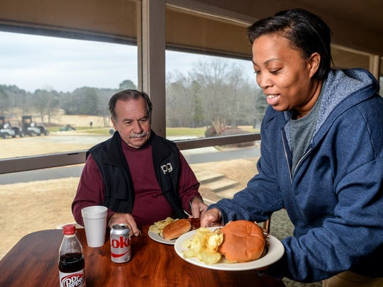 Kiara Johnson, right, serves a barbecue plate to Phil Gibisch of Anderson at Grits and Gravy restaurant, in the clubhouse of Cobbs Glen Country Club in Anderson on Thursday.