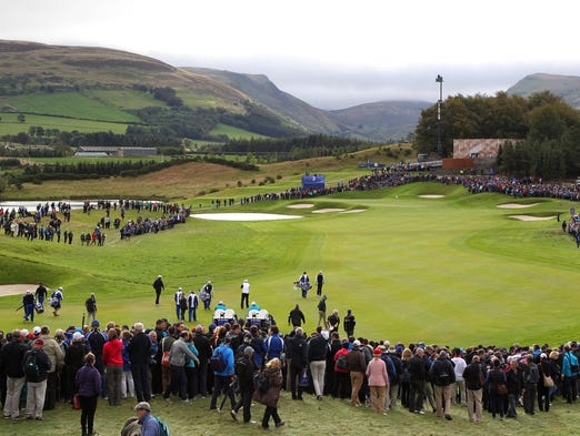 Fans gather to watch European players Rory McIlroy, Sergio Garcia, Martin Kaymer, and Thomas Bjorn play the second hole during practice for the 2014 Ryder Cup at The Gleneagles Hotel-PGA Centenary Course.