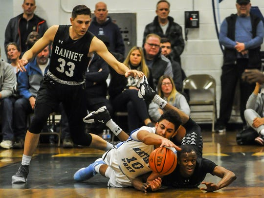 Adam Afifi of Mater Dei Prep, left and Scottie Lewis of the Ranney School, right, dive for the loose ball with Chris Autino watching in the background in a game on Feb. 5 in Middletown.