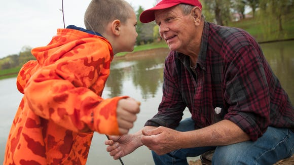 "Kevin Fix Jr., 7, pleads with his grandfather, Nelvin Fix, to go home and pick up his skateboard during a fishing trip to Lake Tams at Gypsy Hill Park on Wednesday, April 15, 2015. ""He's exactly like my sons were, they get the line wet and next thing you know they're throwing rocks,"" said the elder Fix, describing his energetic grandson's impatience with waiting for a bite."