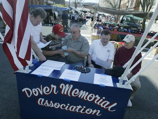 Left-Robert Wangner, then-President of the Dover Memorial Association, Tucker Poolas 9, with his father, Frank Poolas Vice President, Jack Delaney  a member and Alderman, and Paul Downs a member of the Dover Memorial Association selling raffel tickets to support the association at the Dover Flea Market in 2007.