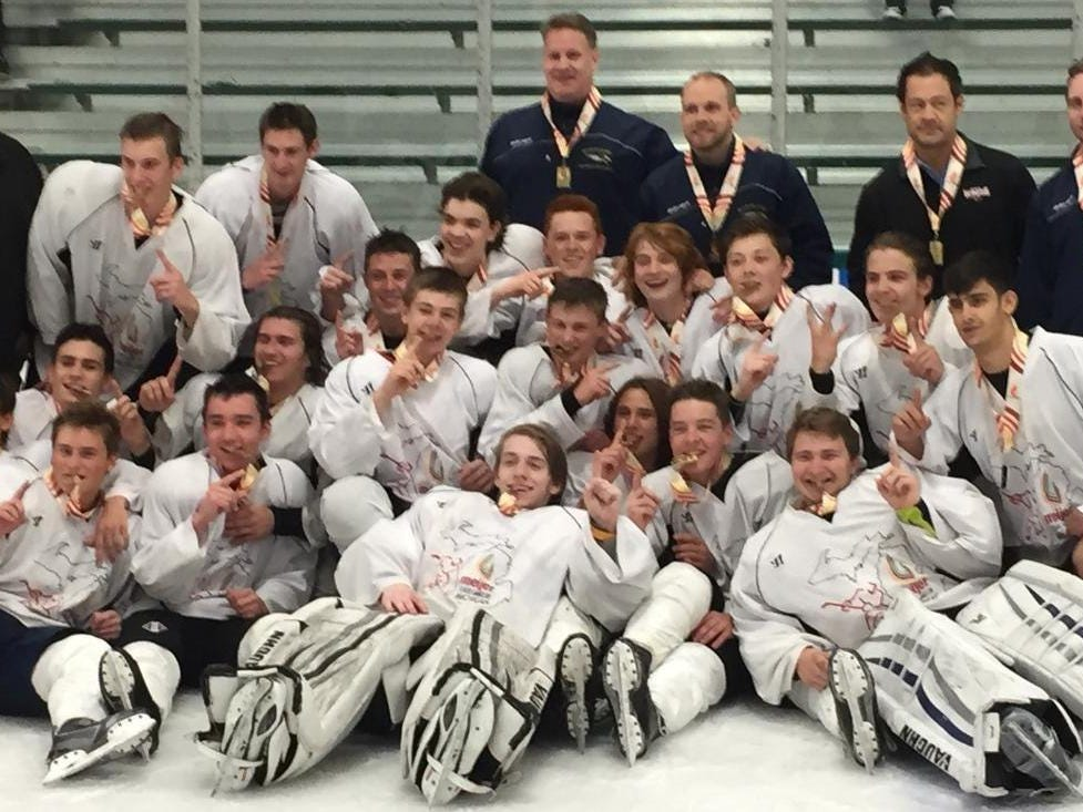 Team Metro West hockey players and coaches celebrate their gold-medal victory in the Meijer State Games.