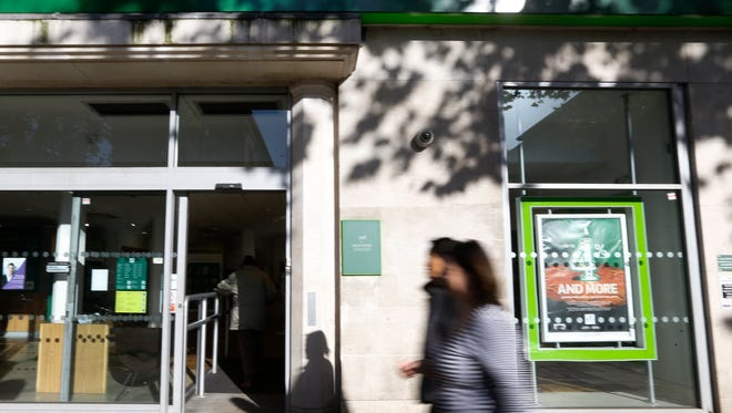 Pedestrians walk past a branch of Lloyds Bank in London on Oct. 28.