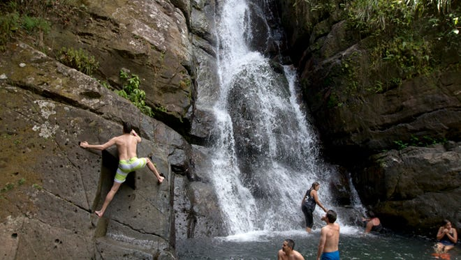 "Visitors at ""La Mina Fall"" in El Yunque National Forest in Puerto Rico, climb atop a rock ledge to get a better vantage point for diving into the water Friday afternoon."