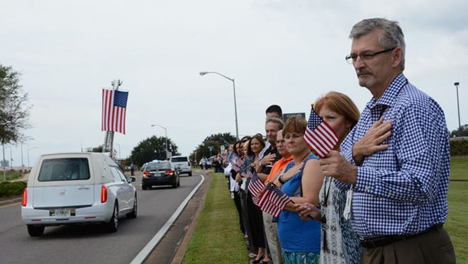 Gulf Power facilities manager Bob Cordes, right, joins dozens of other employees in a final salute to Staff Sgt. Forrest Sibley as his funeral procession passed the Corporate Office on Bayfront Parkway in September 2015.
